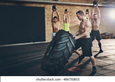 Muscular shirtless man moving large tire while four other athletic adults lift kettle bell weights above their heads during cross fit training at gym