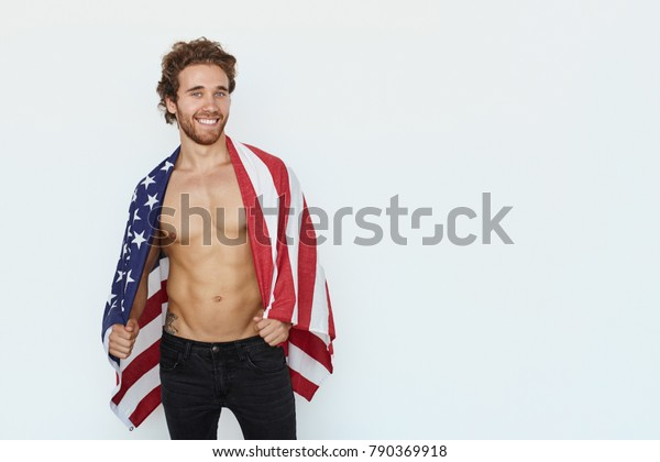 Muscular shirtless man posing with American flag on shoulder looking alluringly at camera.