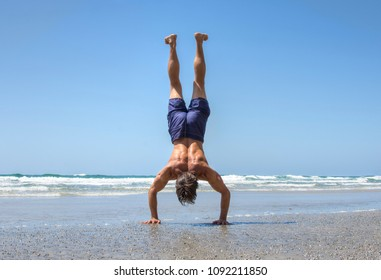 Muscular shirtless man presses body in handstand position on sunny day at sandy beach