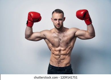 Muscular shirtless man wearing box gloves with hands raised ready to struggle, looking at camera