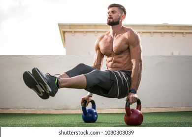 Muscular shirtless man workout with kettle bells in  L Sit position at rooftop gym.