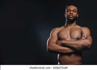 muscular shirtless young african american man standing with crossed arms and looking at camera isolated on black