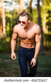Muscular smiling young man in sunglasses.