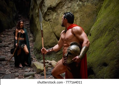Muscular Spartan warrior with stunning ripped strong body walking away from his wife looking at her with love goodbye relationships love people medieval couples romance affectionate.