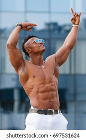 A muscular sports guy with a beautiful body. Hot Man posing among city buildings. Athletic man fitness model with a sports body. A guy in sunglasses on the street among buildings and shop windows.