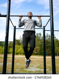 Muscular sports trainer on street workout exercising. Fit and athletic man working out in an outdoor gym. Pull ups on horizontal bar.