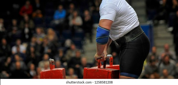 muscular sportsman doing farmer's walk exercise during his competition workout. Strongman sport