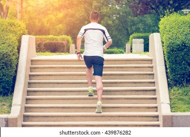 Muscular sportsman running up on stairs. Morning workout. Urban scene. Fitness, sport, recreation, workout, healthy lifestyle concepts.