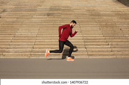 Muscular sportsman running stairs background. Morning workout. Urban scene. Fitness, sport, recreation, workout, healthy lifestyle concepts.