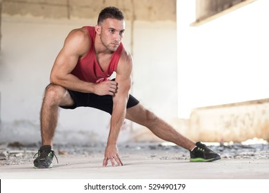 Muscular sportsman stretching out before a sports training in an abandoned ruin building