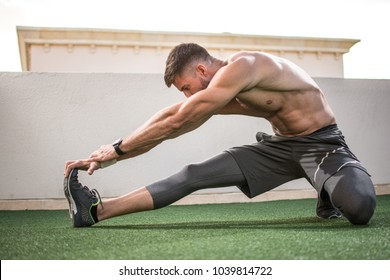 Muscular sportsman warming up before sports training outdoors.