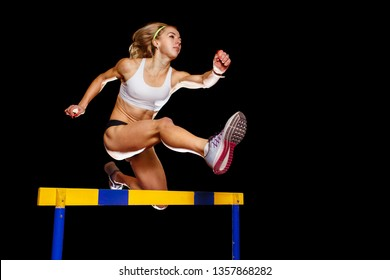 Muscular sportswoman jumping over hurdle on sprint race isolated on black background. Track and field event concept image