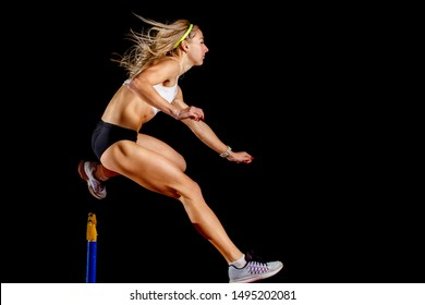 Muscular sportswoman jumping over hurdle on sprint race isolated on black background
