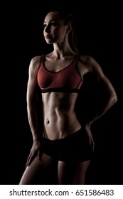 muscular sportswoman posing in sportswear and showing her slim body isolated on black