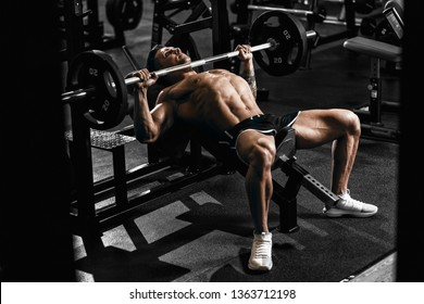 Muscular tattoo man bodybuilder training in gym and posing. Strong man  workout with barbell on bench