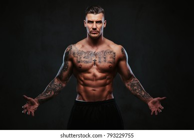A muscular tattooed man on a dark background.
