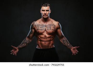 Un homme tatoué musclé sur fond noir.