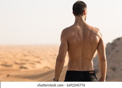 Muscular topless handsome fit man standing above the desert landscape view. Back view.