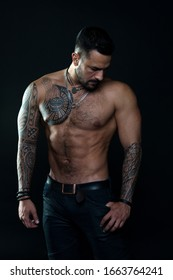 Muscular torso. Jewelry for real men. Bearded man with tattooed torso. Macho sexy bare torso. Fit model with tattoo art skin. Sportsman or athlete with beard and hair. Sport and fitness. Masculinity.