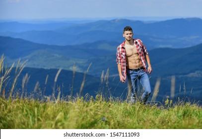 Muscular tourist walk mountain hill. Hiker muscular torso reach mountain peak. Athlete guy relax mountains. Beautiful environment. Hiking concept. Man stand top mountain landscape background.