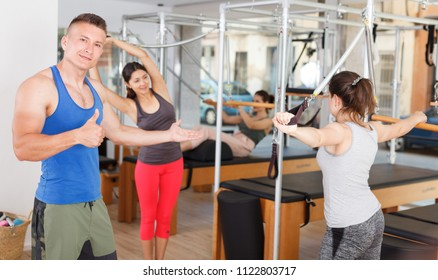 muscular trainer with a group of girls in the modern gym doing exercises