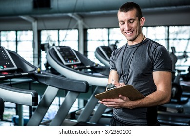 Muscular trainer writing on clipboard at the gym