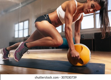 Muscular woman doing intense core workout in gym. Strong female doing core exercise on fitness mat with medicine ball in health club.