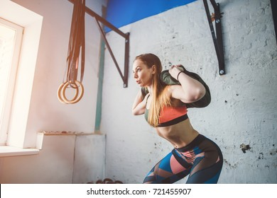 muscular woman doing lunges with a sand bag.