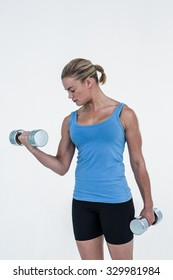 Muscular woman exercising with dumbbells on white background