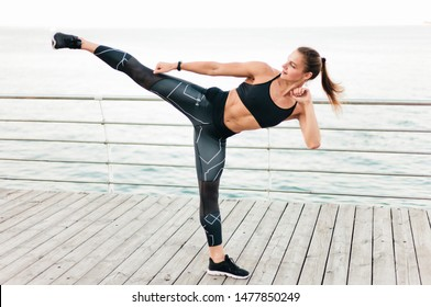 Muscular woman fighter in sportswear makes kick on the beach terrace against the sea