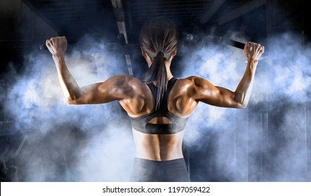 Muscular woman in fitness hall pulled on the bar. Back training