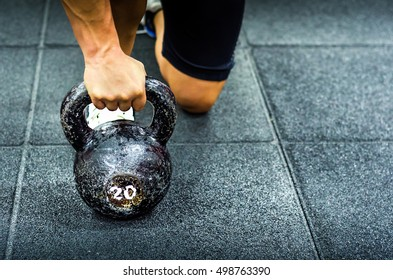 Muscular woman holding old and rusty kettlebell on to the gym floor for fitness training, real people workout no posing