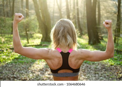 Muscular woman showing her body outdoor.
