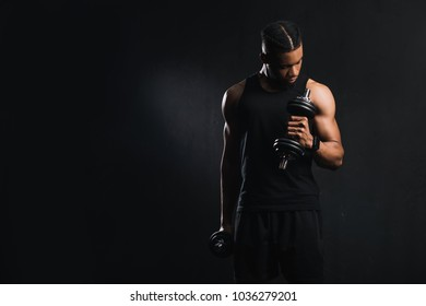 muscular young african american man in sportswear exercising with dumbbells isolated on black