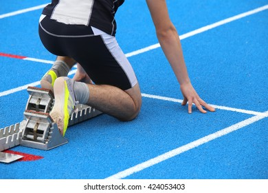 muscular young athlete in the starting blocks of a athletic track before the start of running race