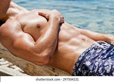 Muscular young athletic sexy man lying on the beach with a naked torso in underwear
