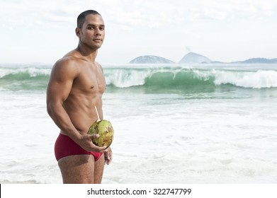 Muscular young carioca Brazilian man wearing red sunga bathing suit holding green coco gelado drinking coconut on Ipanema Beach in Rio de Janeiro, Brazil