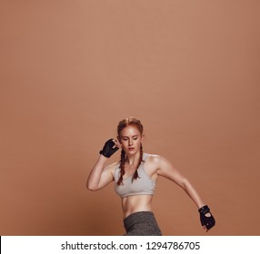 Muscular young female athlete exercising on brown background. Woman athlete doing stretching workout.