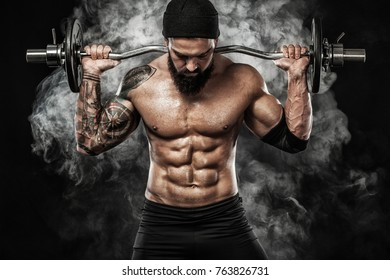 Muscular young fitness sports man workout with barbell in fitness gym