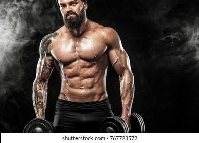 Muscular young fitness sports man workout with dumbbell in fitness gym