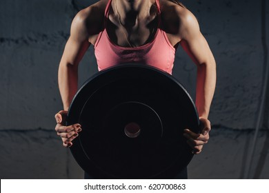 Muscular young fitness woman lifting a weight crossfit in the gym. Fitness woman deadlift barbell. The gym on the red wall is written SPORT. Crossfit woman. Crossfit style.