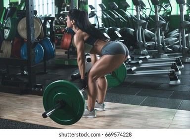 Muscular young fitness woman lifting a weight crossfit in the gym. Fitness woman deadlift barbell. Rear viw. Crossfit woman. Crossfit style. Crossfit and fitness