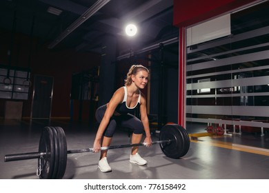 Muscular young fitness woman lifting a weight cross fit in the gym. Fitness woman deadlift barbell