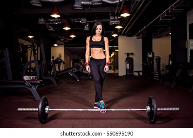 Muscular young fitness woman preparing for heavy deadlift exercise in gym