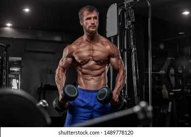 Muscular young guy trains with two dumbbells. Studio photo with dark wall background