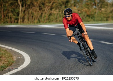 Muscular young guy wearing sport clothing, protective helmet and mirrored glasses enjoying sport activity on black bike. High speed and racing.