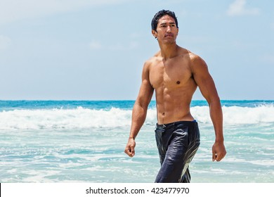 Muscular young Hawaiian man walking in the surf