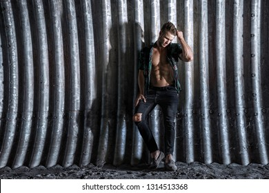 Muscular young man with beard on dark tunnel urban background. Fashion portrait of brutal strong muscle guy in modern trendy clothes. Model, fashion concept. Sexy naked torso, six pack abs.