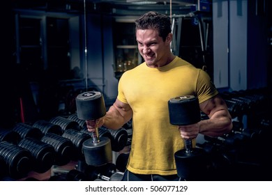 Muscular young man bodybuilder lifting weights on gym background