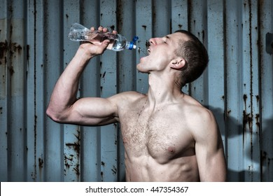 Muscular young man drinks water after sport exercise